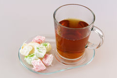Sweet jelly cubes and tea. Sweet jelly cubes and cup of tea on white background Royalty Free Stock Photo