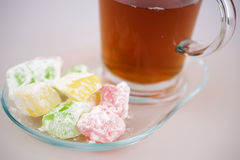 Sweet jelly cubes and tea. Sweet jelly cubes on plate and cup of tea Royalty Free Stock Image