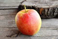 Sweet juicy apple  on old wooden background. A large red apple. Closeup Royalty Free Stock Photography