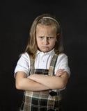 Sweet junior schoolgirl with blonde hair crying sad in front of school classroom blackboard Stock Images
