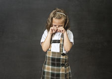 Sweet junior schoolgirl with blonde hair crying sad in front of school classroom blackboard Royalty Free Stock Images