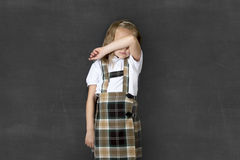 Sweet junior schoolgirl with blonde hair crying sad and shy in front of school class blackboard Royalty Free Stock Images