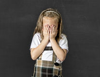 Sweet junior schoolgirl with blonde hair crying sad and shy in front of school class blackboard stock photo