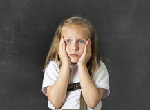 Sweet junior schoolgirl crying sad in children education stress and bullying victim. Young sweet junior schoolgirl with blonde hair crying sad and shy standing Stock Image