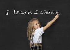 Sweet junior schoolgirl standing happy writing in blackboard I learn science royalty free stock photo