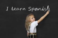 Sweet junior schoolgirl standing happy writing in blackboard I learn Spanish stock image