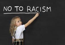 Sweet junior schoolgirl writing with chalk no to racism in school classroom blackboard Stock Photos