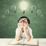 Sweet kid looking at bright light bulb Stock Image