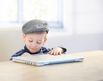 Sweet kid sitting at table in cap with laptop Stock Photography