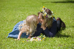 Sweet kiss. Mum and daughter lie on a green grass, the daughter kisses mum stock photos