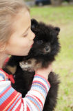 Sweet Kiss. Little girl gives this pomeranian puppy a kiss to the side of her face as the it looks away Stock Images