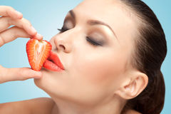 Sweet kiss. A creative portrait of a beautiful girl kissing a fresh strawberry with delicious red lips Royalty Free Stock Photography