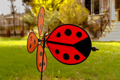 Sweet ladybird weathercock in the green garden Royalty Free Stock Photo