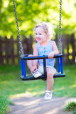 Sweet laughing toddler girl swinging ride on playground Stock Photos