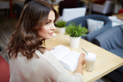 Sweet laziness with book. Back portrait of young pretty lady reading book at cafe Stock Photo