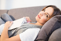 Sweet laziness with book. Close up portrait of beautiful woman lying on couch with book Royalty Free Stock Image