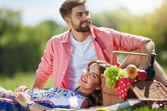 Sweet laziness. A photo of young, happy couple relaxing on the picnic at the park Royalty Free Stock Images