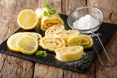 Sweet lemon roll with curd, with mint and powdered sugar close-up. horizontal. Sweet lemon roll with curd, with mint and powdered sugar close-up on the table stock photos