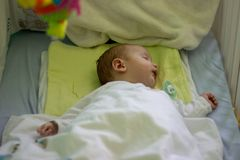 Sleeping babyboy in cot royalty free stock photo
