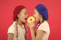 Sweet life. Sweets shop and bakery concept. Kids fans of baked donuts. Share sweet donut. Girls in beret hats hold donut. Red background. Kids playful girls royalty free stock photos