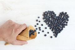 Sweet Like follower. Hand with waffle cones, from which poured the berries in a heart, top view Royalty Free Stock Image