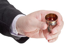 Sweet liquor in silver glass in male hand Stock Image