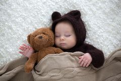 Sweet little baby boy, dressed in handmade knitted brown soft te. Ddy bear overall, sleeping cozy at home in sunny bedroom with lots of teddy bears around him Stock Images
