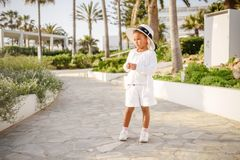 Sweet little baby girl in beautiful dress, summer hat plays walks outdoors on warm sunny summer day royalty free stock photo