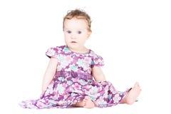 Sweet little baby girl in a festive purple dress Stock Photo