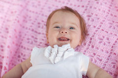 Sweet little baby girl lying on her back. Sweet little baby girl lying on her back wearing a white jacket, looking at the camera and laughing  back Stock Images