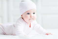 Sweet little baby girl lying on her tummy and knitted hat royalty free stock images