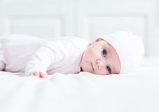 Sweet little baby girl lying on her tummy and knitted hat Royalty Free Stock Photography