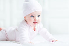 Sweet little baby girl lying on her tummy and knitted hat Stock Image