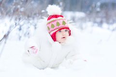 Sweet little baby girl playing in snow park stock photos