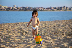 Sweet little baby playing with bright sand toy on beach Royalty Free Stock Image