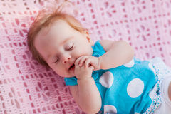Sweet little baby sleeping. She in blue dress with white polka dots Royalty Free Stock Images