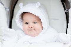 Sweet little baby in a teddy bear hat sitting in a white stroller on a cold winter day Stock Photo