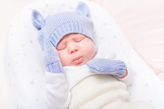Sweet little baby wearing knitted blue hat with ears and mittens. Lying in beautiful cradle with closed eyes and making sad face. Security and childcare concept royalty free stock photos