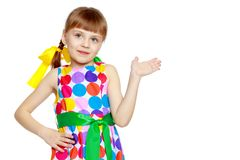 Little girl gesticulating. A sweet little blonde girl with long pigtails, in which large colored bows are braided, and a short bangs on her head. In a short Royalty Free Stock Image