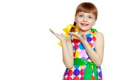 Little girl gesticulating. A sweet little blonde girl with long pigtails, in which large colored bows are braided, and a short bangs on her head. In a short Stock Images