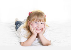 Sweet  little blonde girl lying happy on bed Royalty Free Stock Photo