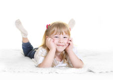 Sweet  little blonde girl lying happy on bed Royalty Free Stock Photography