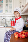 Sweet little boy, dressed as a chef, eating and cutting apples f Royalty Free Stock Image