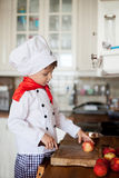 Sweet little boy, dressed as a chef, eating and cutting apples f Royalty Free Stock Photos