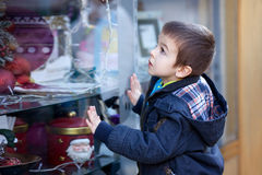 Sweet little boy, looking through a window in shop, decorated fo Stock Photos