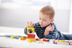 Sweet little boy lost in playing. Sweet little boy laying on floor, playing with building cubes Royalty Free Stock Images