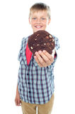 Sweet little boy offering you a chocolate cookie Stock Images
