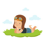 Sweet little boy in pilots helmet lying on his stomach on a grass and dreaming, kids imagination and fantasy, colorful Stock Image
