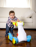 Sweet little boy playing alone with baby walker taking his first steps excited and playful Stock Images