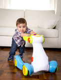 Sweet little boy playing alone with baby walker taking his first steps excited and playful Royalty Free Stock Images